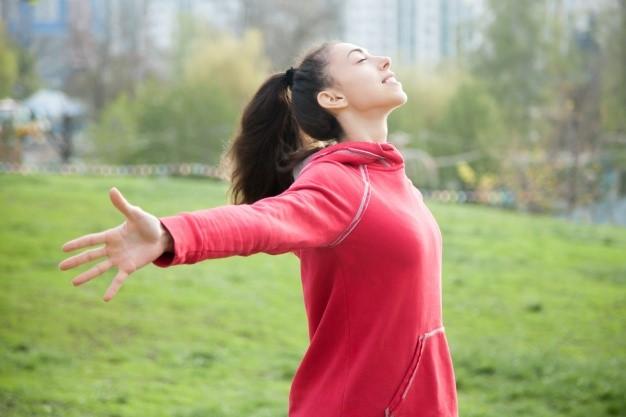 Femme respirant à bras ouverts